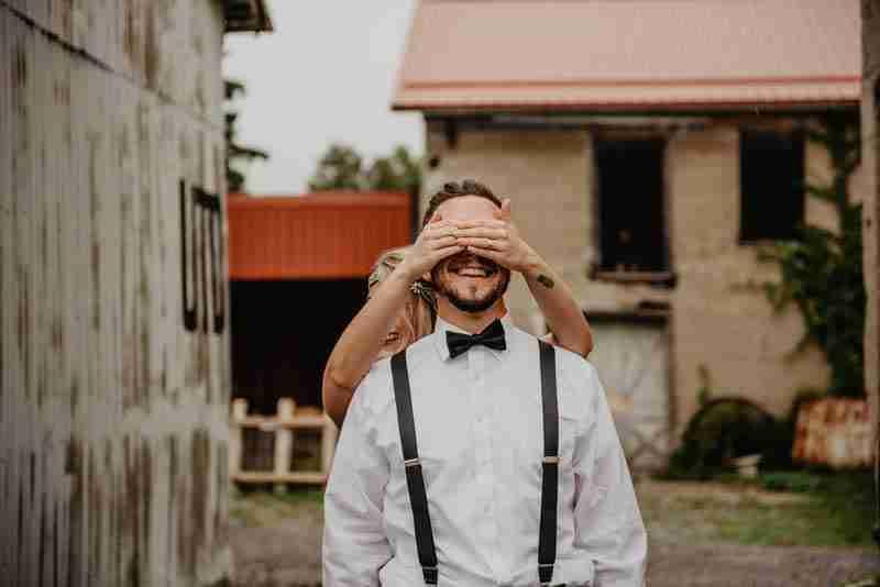 Bride holding hands over groom's eyes.