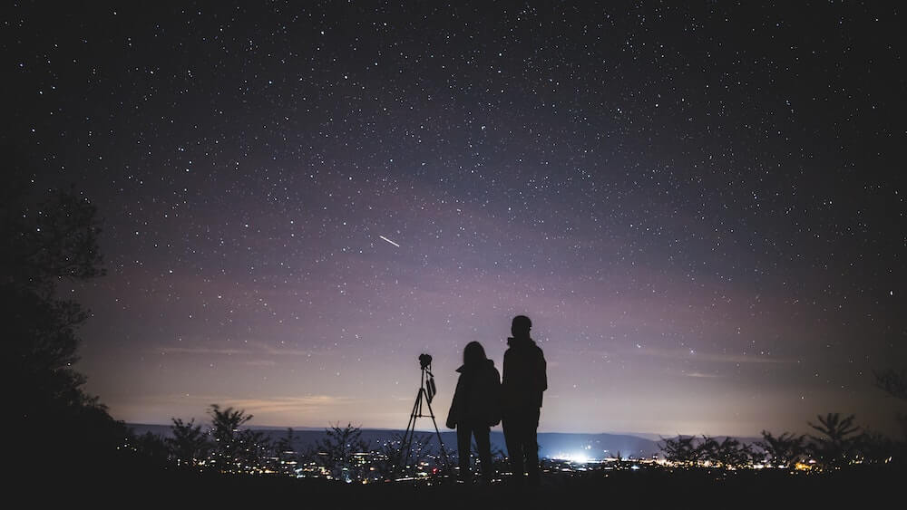 Two people stargazing next to camera.
